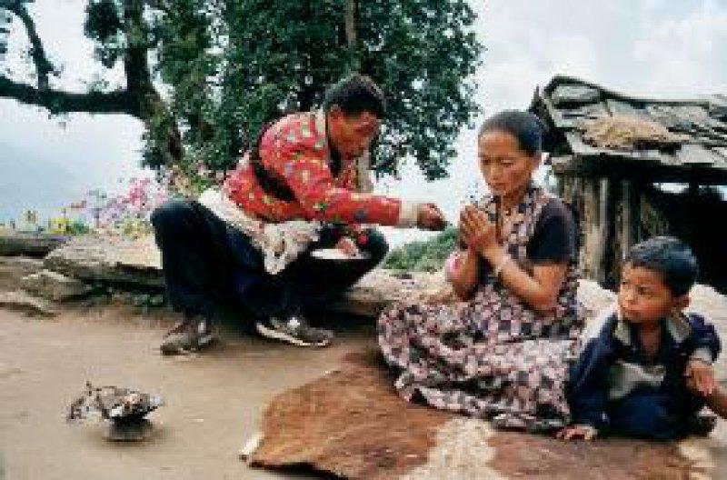 Der Schamane Myingmar Sherpa bei einer Heilzeremonie: Er behandelt den starken Husten seiner Schwiegertochter und seines Enkels. Fotos: Susanne Thor