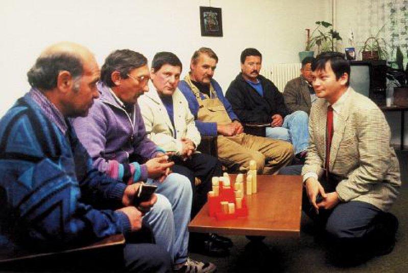 Ungewöhnliche Therapiemethode: Dr. Holger Lux (rechts) bei einer Gruppensitzung, in der mithilfe von Holzfiguren eine Familienaufstellung vorgenommen wird.
