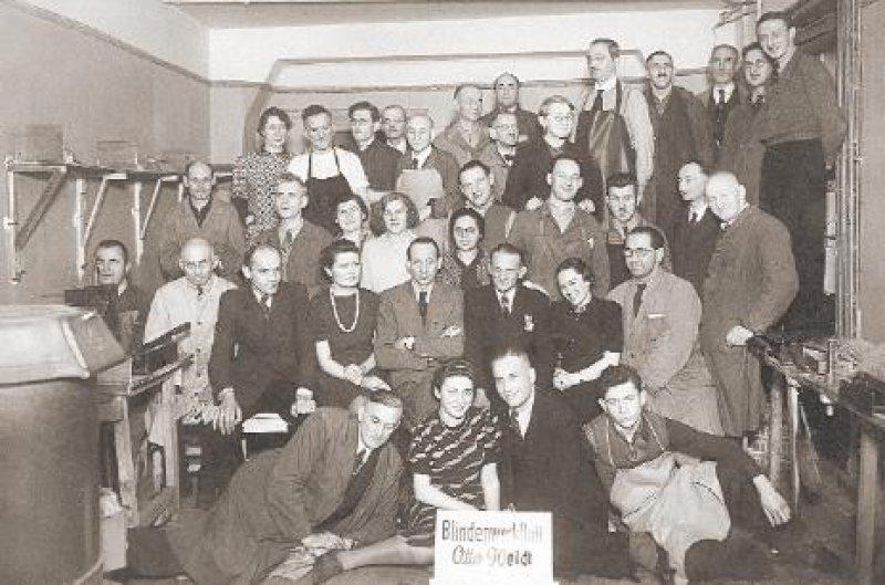 """Die Blindenwerkstatt im Jahre 1942. Die Zweite von links in der ersten Reihe ist Inge Deutschkron. Otto Weidt, der Chef des """"wehrwichtigen"""" Betriebes, ist der Sechste von links in der zweiten Reihe, Alice Licht ist die Frau rechts neben Weidt. Fotos: Museum Blindenwerkstatt Otto Weidt"""