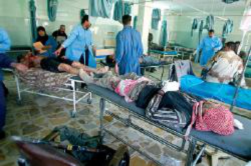Verletzte irakische Soldaten in einem Krankenhaus in Bagdad. Unten links: eine Kalaschnikow Foto: dpa