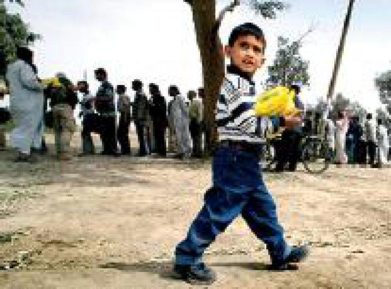Der kleine irakische Junge freut sich über ein Lebensmittelpaket. Foto: dpa