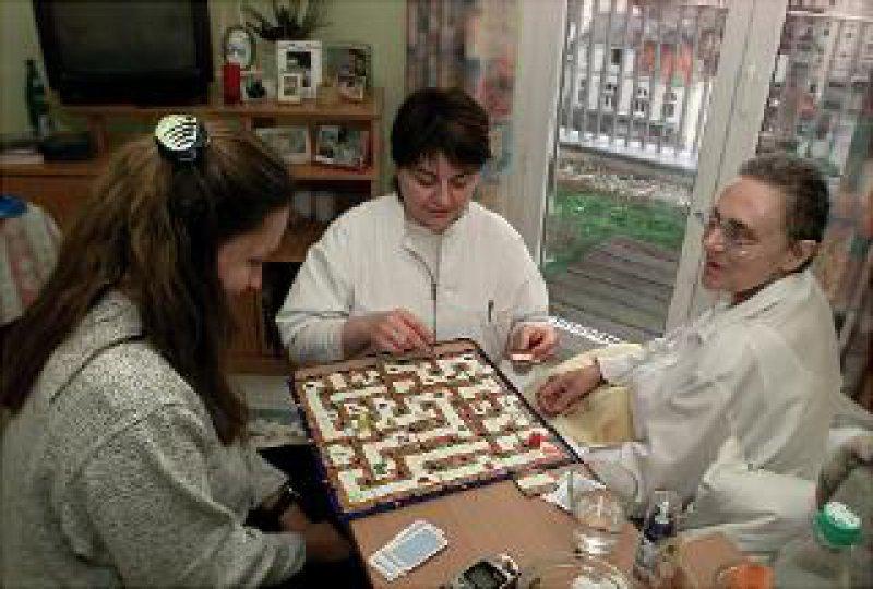 """Ricam-Hospiz in Berlin: Eine Besucherin und eine Pflegerin spielen mit einer Patientin """"Das verrückte Labyrinth"""". Foto: KNA"""