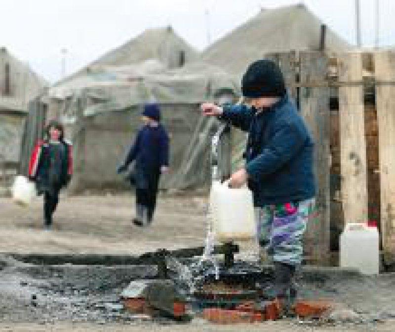 Ein Junge füllt im Flüchtlingslager Karbulak Trinkwasser ab. Das Lager in Inguschetien liegt im Grenzgebiet zu Tschetschenien. Foto: dpa
