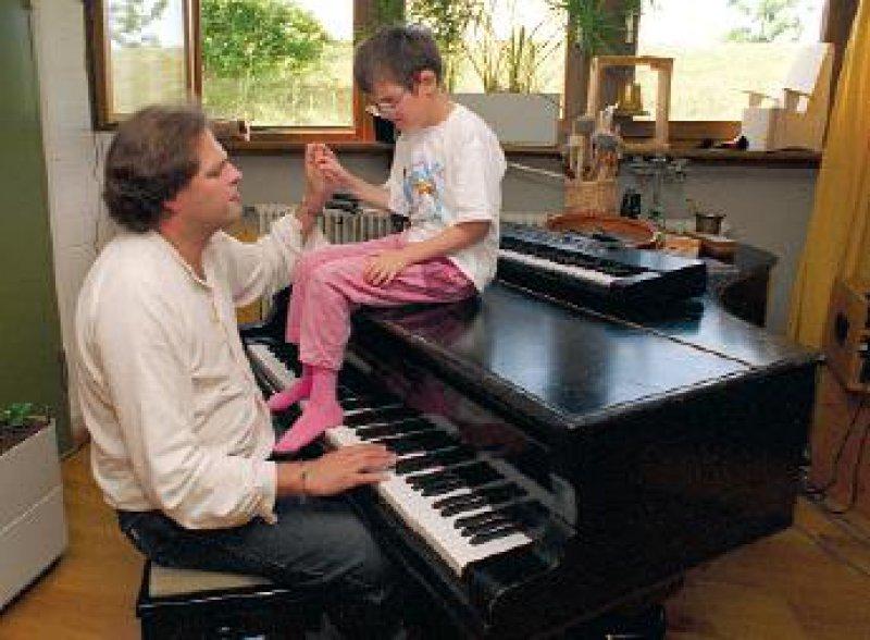 Musiktherapie für geistig behinderte Kinder: Dass die zehnjährige Ina nur mit den Füßen mitspielt, ist für den Diplom-Musiktherapeuten des Würzburger Blindeninstituts, Markus Rummel, schon ein Erfolg. Foto: dpa