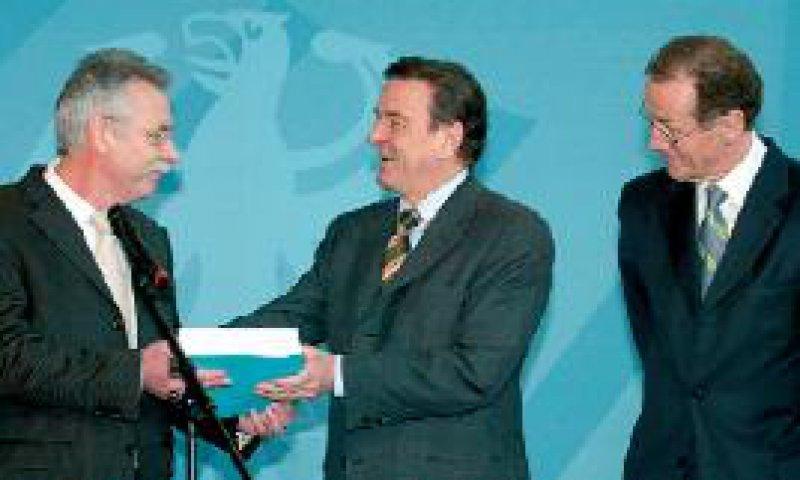 Wolfgard Wiegard (l.) und Bert Rürup überreichen das Gutachten an Bundeskanzler Gerhard Schröder. Foto: dpa