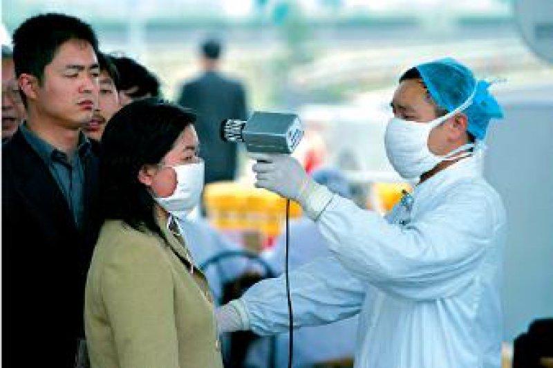 Aufwendige Schutzmaßnahmen in Schanghai 2003: Um SARS-Verdachtsfälle herauszufiltern, wird bei Pendlern die Temperatur gemessen. Foto: dpa
