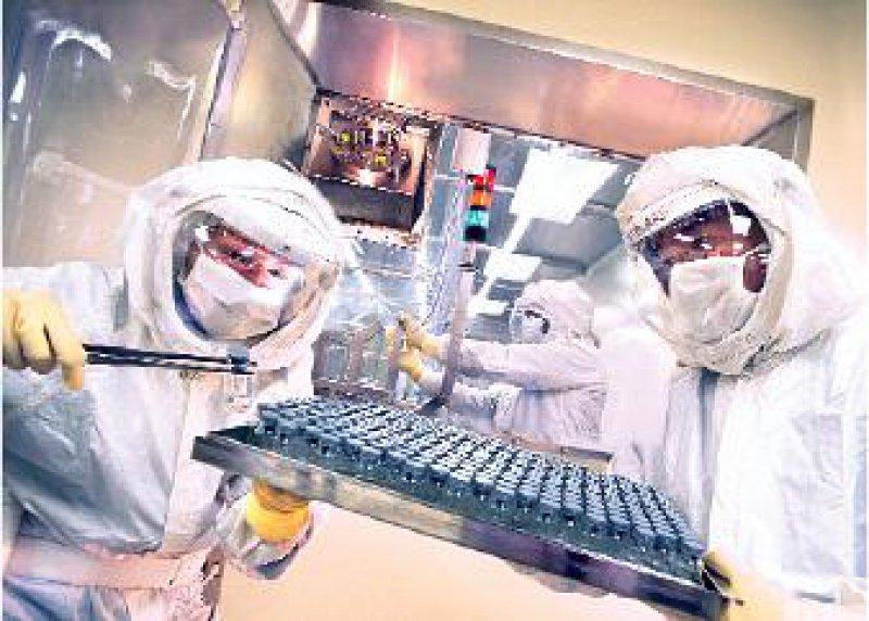 Mitarbeiter in gasdichten Anzügen bei der Sichtung des gefriergetrockneten rFVIIIKuchens. Foto: Bayer