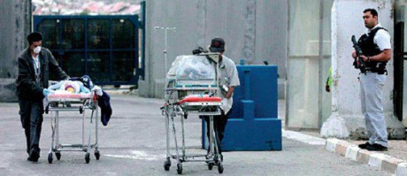 Erez Crossing: Palästinensische Krankenpfleger schieben zwei Kinder über die Grenze. Sie sollen in Israel operiert werden. Nicht immer verläuft der Transfer von Kranken so reibungslos. Foto: dpa