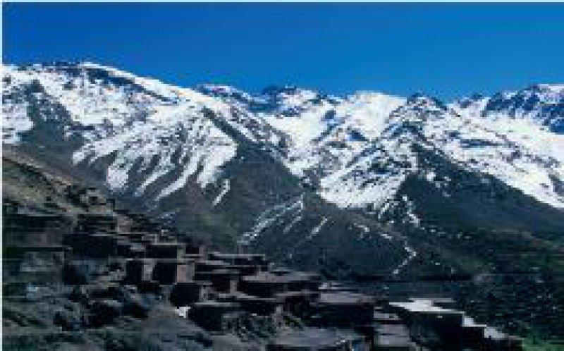 Kontraste: Karstig und staubig ist es im Dorf Tacheddirt, dahinter liegen die schneebedeckten Gipfel von Igouenouane und Dschebel Likemt.