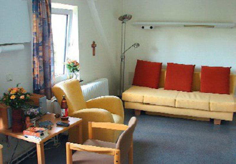 """Angehörige und Erkrankte können die """"Rückzugszimmer"""" aufsuchen, die mit Schlafsofa, Sessel, Couchtisch und Schrank eingerichtet sind."""