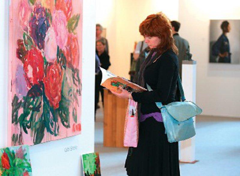 Impressionen von der Art Karlsruhe – rechts eine Messebesucherin vor einem Werk von Gabi Streile. Fotos: Art Karlsruhe