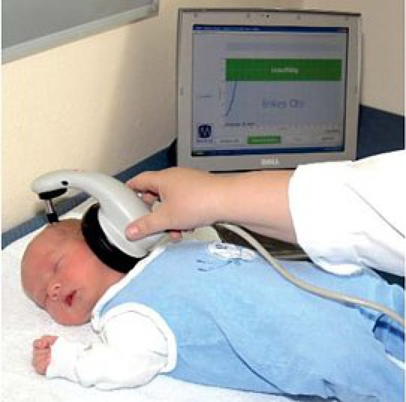 Figure: Automated evaluation of auditory evoked potentials with an AABR (automated auditory brainstem response) system for neonatal auditory screening. The examiner holds a loudspeaker containing built-in electrodes to the ear of a 3-day-old child. The auditory stimuli and the automated evaluation of the response are processed by a computer program (PC in the background). Positive results must be confirmed by further diagnostic testing. All results are reported to a coordinating office and are also documented in the child's yellow preventive care booklet, along with an identifying number.