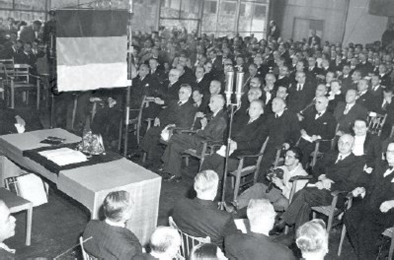 Das Grundgesetz unter der schwarzrot- goldenen Standarte. Am 23. Mai 1949 tritt der Parlamentarische Rat zum letzten Mal zur feierlichen Unterzeichnung zusammen. Foto: dpa