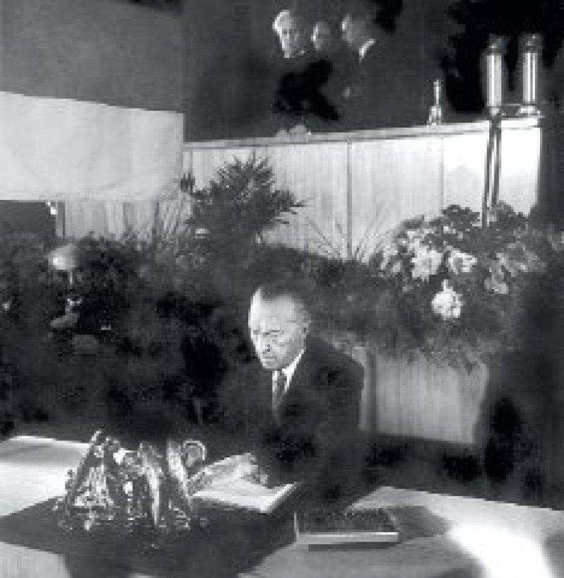Konrad Adenauer, der Präsident des Parlamentarischen Rates, setzt seinen Namen unter das Grundgesetz. Foto: dpa