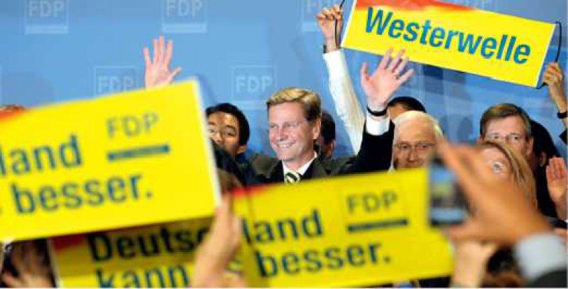 Alles im gelben Bereich: Guido Westerwelle und Anhänger der Liberalen freuen sich. Foto:ddp