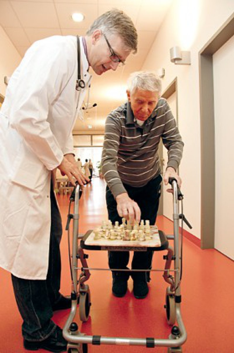 Spaß an der Arbeit mit alten Menschen: Chefarzt Ralf-Joachim Schulz bei einer kurzen Schachpartie auf dem Stationsflur. Fotos: jardai/modusphoto