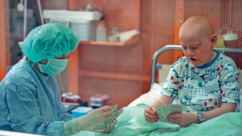 Ein elfjähriger krebskranker Junge beim Kartenspiel mit seiner Mutter. Er wartet auf eine Stammzelltransplantation. Foto. Picture Alliance