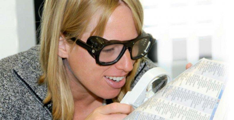 Selbsterfahrung (I): Eine nichtärztliche Mitarbeiterin liest das Fernsehprogramm mit einer Brille, die eine Sehbehinderung simuliert.