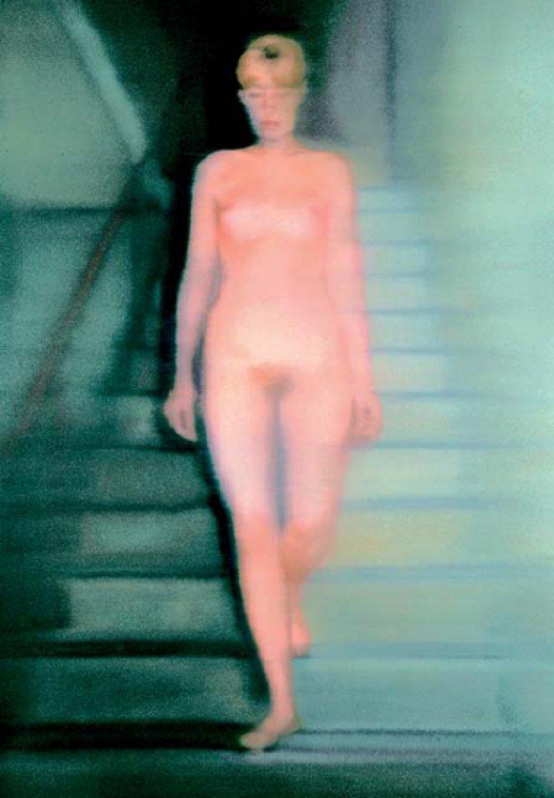 """Gerhard Richter, """"Ema – Akt auf einer Treppe"""", 1966, Öl auf Leinwand, 200 × 130 cm: Eine junge, nackte Frau schreitet, die Augen unter dem blonden Pony niedergeschlagen, vorsichtig eine Treppe hinab. Sie wirkt in sich gekehrt, eher unbeteiligt als erotisch. Obwohl sie auf der Leinwand in Lebensgröße erscheint, ist ihre Körperlichkeit und Nähe eine Illusion. Denn durch das Verwischen der Farbe auf dem Gemälde, das wie ein unscharfes Foto aussieht, entzieht der Künstler die luzide Schöne dem Betrachter. Trotz der Frontalansicht ihres Körpers bleibt sie distanziert. Ihre Gesichtszüge sind nicht genau zu erkennen. Dass sie schwanger ist, bleibt verborgen. Gerhard Richter hat den intimen Moment inszeniert. Als Vorlage für das Aktbild fotografierte er 1966 seine damalige Ehefrau Marianne """"Ema"""" Eufinger im Treppenhaus vor seinem Atelier. © Gerhartd Richter/Schenkung Ludwig 1976"""