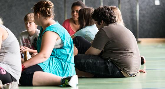 Übergewichtige Jugendliche sitzen in einer Turnhalle. /dpa