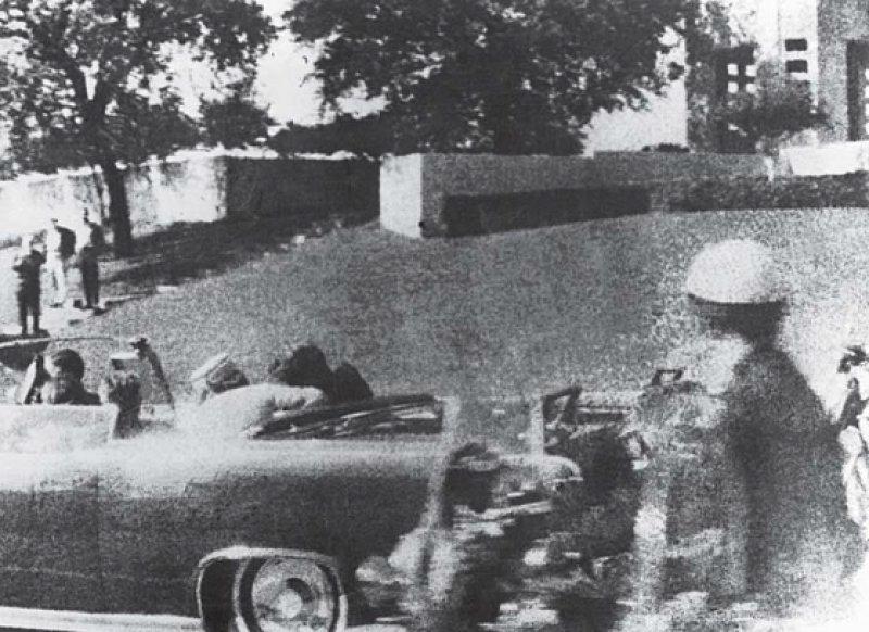 John F. Kennedy sackt nach den Schüssen auf dem Rücksitz der offenen Limousine zusammen (Archivfoto vom 22. November 1963). Neben ihm seine Frau Jacqueline Kennedy, die das Attentat unverletzt überstand. Foto: dpa