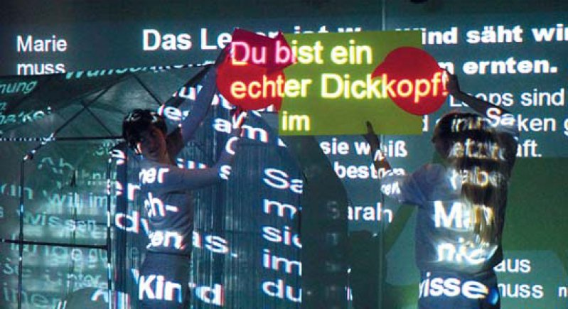 Ein Gewitter von projizierten Titeln bricht über das Bühnengeschehen herein – ein Theater projekt in Hildesheim.