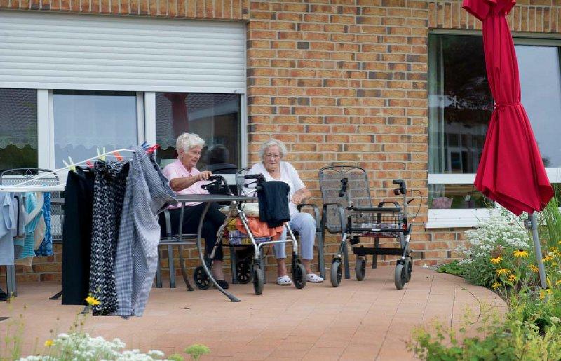 Zwei Bewohnerinnen der Wohnanlage in Tönebön am See genießen die Mittagssonne. Fotos: Jan Haas/picture alliance für Deutsches Ärzteblatt