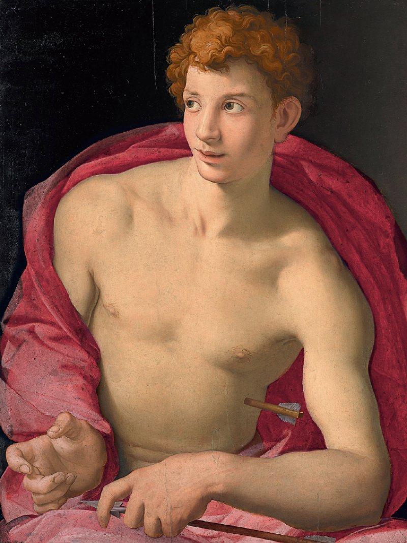 """Agnolo Bronzino: """"Heiliger Sebastian"""", um 1528/29, Öl auf Holz, 87 × 76,5 cm: Der Märtyrer ist hier nicht mit blutenden Wunden und geschundenem Körper dargestellt, sondern als schlanker, schöner Apollo mit gelocktem Haar und verträumtem Augenaufschlag. Dass es sich um den als Pestheiligen verehrten Sebastian handelt, verdeutlicht Bronzino durch die beiden Pfeile als Symbole der Pest. Einen hält der fast nackte Jüngling in seiner linken Hand, der andere durchbohrt seine linke Seite, ohne die ästhetische Unversehrtheit seines Körpers zu beeinträchtigen. Foto: Museo Thyssen-Bornemisza, Madrid"""