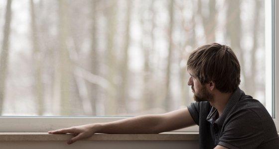 Mann schaut aus dem Fenster. /photographee.eu, stock.adobe.com