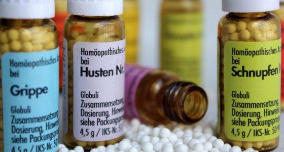Drei Flaschen mit Globuli gegen Grippe, Husten und Schnupfen. /thomas.andri, stock.adobe.com