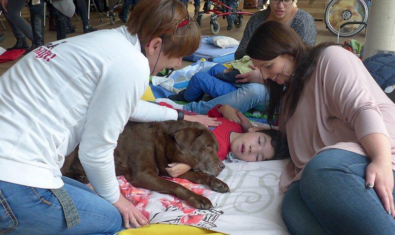Beruhigende Wirkung: Marco mit Therapiehund Emma, Pflegerin Ivana Seger (l.) und seiner Mutter Stephanie (Informationen: www.emmahilft.de)