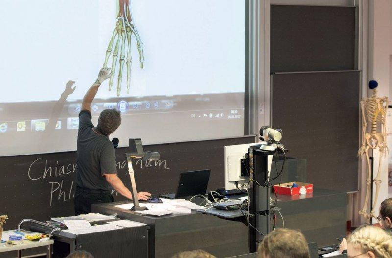 Ein studentischer Mitarbeiter zeichnet die Vorlesungen von Erik Schulte in Mainz auf. Dabei wird die Videoanlage vor dem Dozententisch platziert und mit dem Smartphone geprüft, ob Farbe und Ton der Übertragung in Ordnung sind. Fotos: Peter Pulkowski