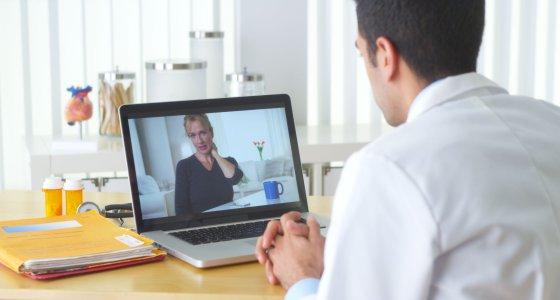 Arzt berät eine Patienten über den Laptop in der Videosprechstunde. /rocketclips, stock.adobe.com