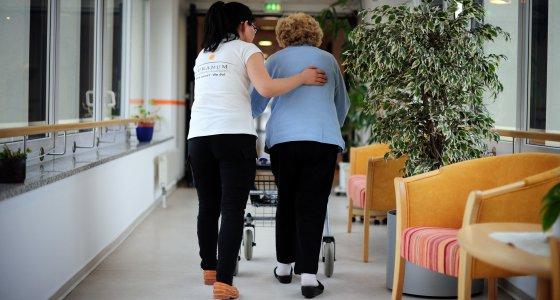 Eine Pflegerin begleitet eine ältere Dame über den Flur eines Krankenhauses. /dpa