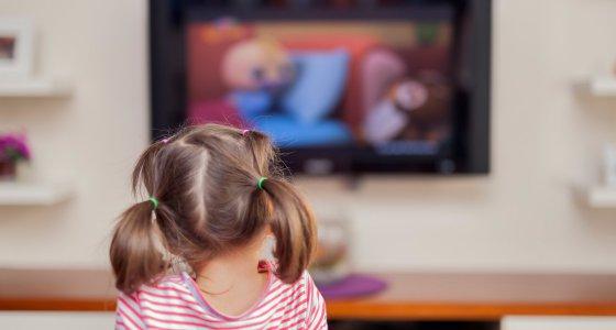 Kind sitzt vor einem großen Bildschirm und schaut Fernsehen. /Myst, stockadobecom