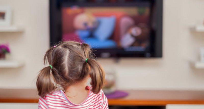 Junges Mädchen sitzt vor dem Fernseher. /Myst, stockadobecom