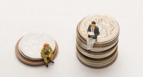 Zwei Männer sitzen auf zwei unterschiedlich hohen Münzstapeln. /maccc, stock-adobe.com