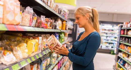 Eine Frau sucht im Supermarkt Produkte aus. /dpa