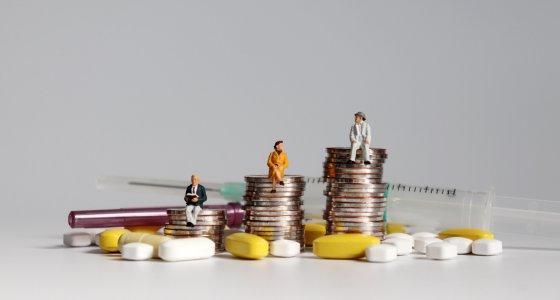 Menschen sitzen auf Münzhaufen umringt von Pillen und Spritzen. /Hyejin Kang, adobe.stock.com