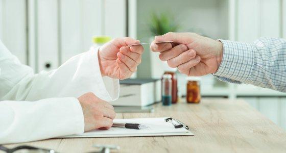 Patient übergibt dem Arzt seine Versicherungskarte. /Bits and Splits stock.adobe.com