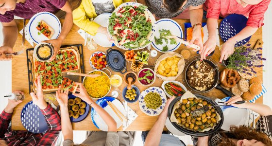 Junge Leute essen gemeinsam ein vegetarisches Essen am Tisch. /Photographee.euadobe.stock.com