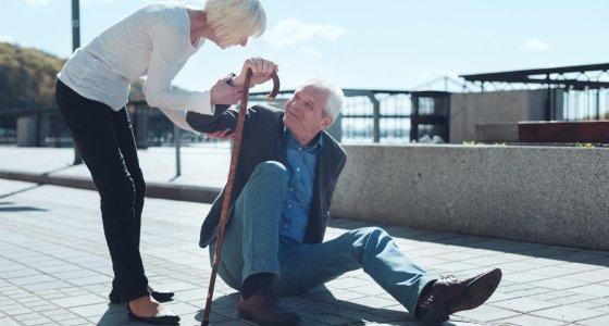 Älterer Mann ist gestürtzt, eine ältere Dame hilft ihm aufzustehen. /zinkevych, AdobeStock.com