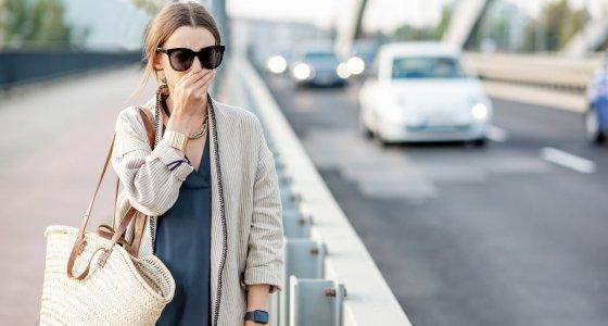 Frau Läuft entlang einer mit Autos befahrenen Straße und hält sich die Hand vor Nase und Mund. /rh2010 AdobeStock.com