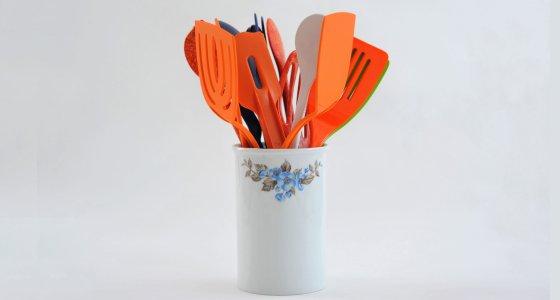 Behälter mit bunten Küchenutensilien aus Kunststoff vor hellem Hintergrund. /picture alliance