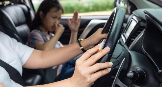 Frau raucht eine Zigarette im Auto, ein Kind sitzt auf dem Beifahrersitz. /Satjawat, AdobeStock.com