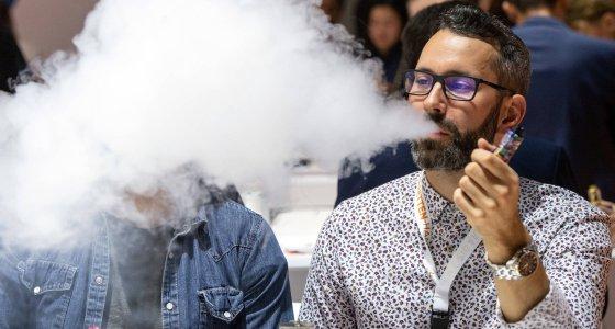 Steve raucht auf seinem Messestand der Messe InterTabac eine E-Zigarette und bläst den Rauch aus. /picture alliance