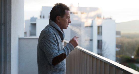 Mann raucht auf dem Balkon /Halfpoint, stock.adobe.com