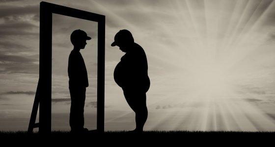 Dicker Junge steht sein schlankes Ebenbild im Spiegel. /Prazis Images, stock.adobe.com