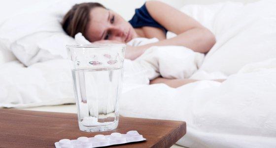 Frau mit Schmerzen liegt im Bett, vor ihr ein Glas mit Tabletten. /corepics, adobe.stock.com