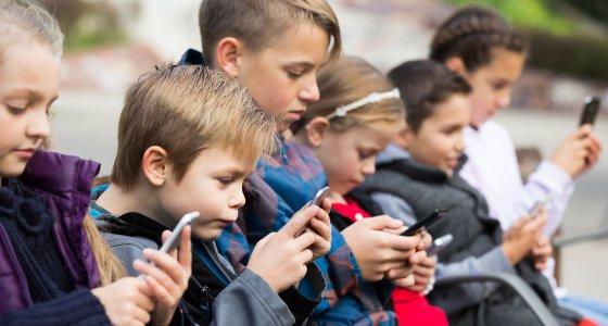 Kinder sitzen in einer Reihe und starren auf ihre Smartphones. /JackF, stockadobecom